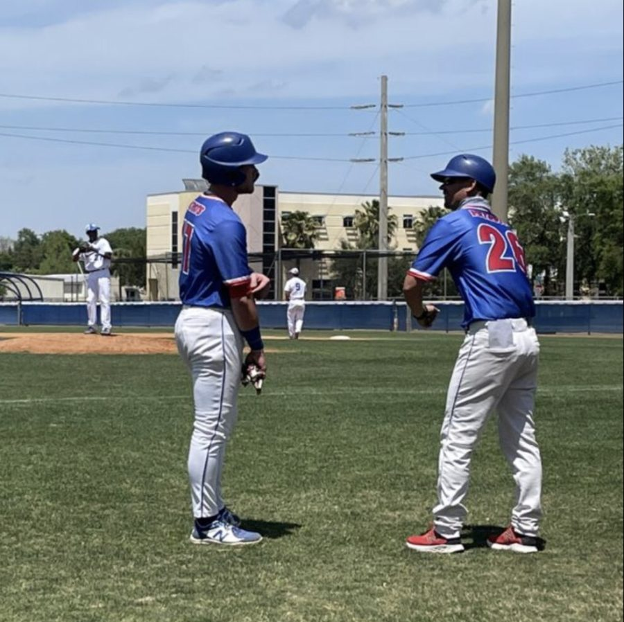 Assistant Coach Jon Koenigsfeld and Outfielder Garett Wallace talk during a game. The Patriots would finish the year 37-15.